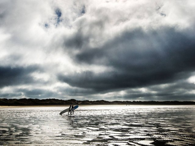 Surfers head for the sea at Saunton Sands, North Devon. (Photo by Neil Squires/PA Wire)