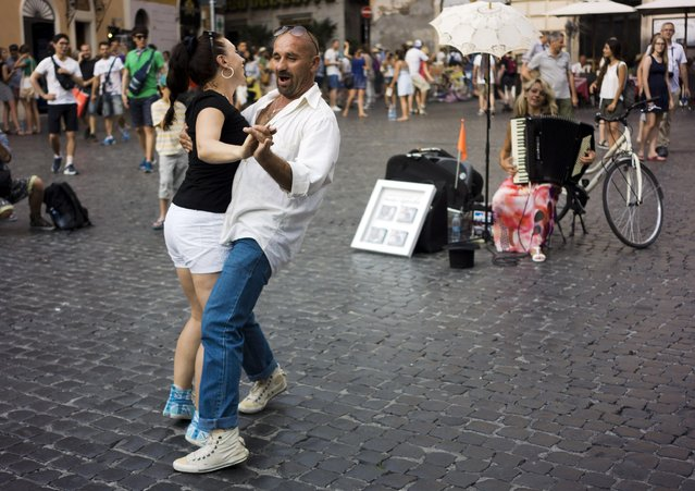 A man and a woman start dancing as they walk by a street performer playing Libertango by Argentine composer Astor Piazzolla, with her accordion in downtown Rome, Tuesday, July 7, 2015. (Photo by Domenico Stinellis/AP Photo)