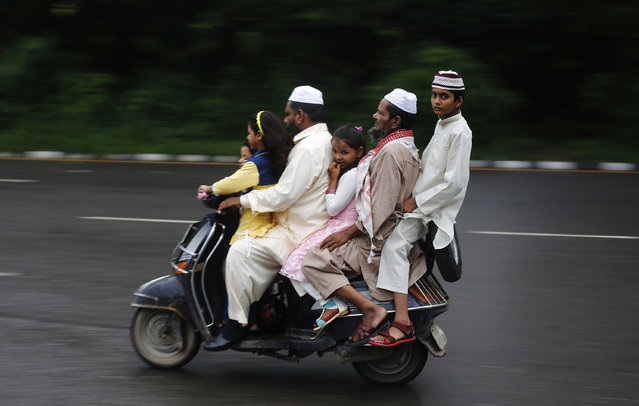 Muslims ride on a scooter on their way to offer prayers at the ruins of Feroz Shah Kotla mosque on the occasion of Eid al-Fitr in New Delhi August 9, 2013. (Photo by Adnan Abidi/Reuters)
