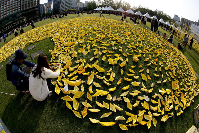 South Korean citizens display yellow paper boats wishing for the safe return of the sunken Sewol ferry's missing passengers in front of the Seoul City hall in Seoul, South Korea, May 6, 2014. The South Korean ferry that sank last month was carrying more than three times its maximum cargo weight, a news report quoted investigators as saying May 6, 2014. (Photo by Jeon Heon-Kyun/EPA)