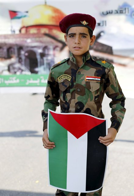 A boy carries a Palestinian flag during a parade marking the annual al-Quds Day, or Jerusalem Day, on the last Friday of the Muslim holy month of Ramadan in Baghdad, July 10, 2015. (Photo by Thaier al-Sudani/Reuters)