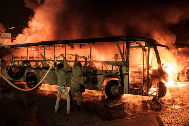 Firefighters try to put out a burning bus set on fire by protesters during the nationwide strike called by unions opposing austerity reforms in Rio de Janeiro, Brazil, on April 28, 2017. Major transportation networks schools and banks were partially shut down across much of Brazil on Friday in what protesters called a general strike against austerity reforms in Latin America' s biggest country. (Photo by Yasuyoshi Chiba/AFP Photo)