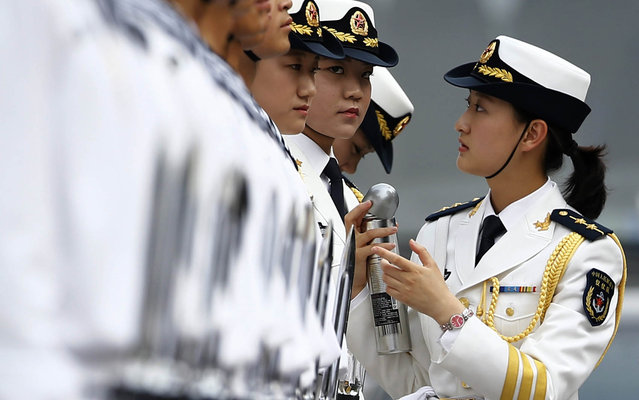 Female soldiers, who started practising as members of honour guards this month, get ready for a welcoming ceremony for the visiting Portugal's President Anibal Cavaco Silva (not seen), outside the Great Hall of the People in Beijing, May 15, 2014. (Photo by Kim Kyung-Hoon/Reuters)