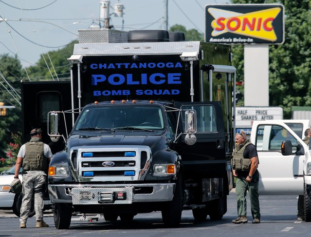Law enforcement work around the Chattanooga Police's bomb squad truck before leaving a staging area on Hixson Pike to investigate the nearby home of Mohammod Abdulazeez in Chattanooga, Tennessee July 16, 2015. Abdulazeez was named by the FBI as the gunman in a shooting at both the Amnicola Highway Armed Forces Career Center and the Naval Operational Support Center. (Photo by Doug Strickland/Reuters/Chattanooga Times Free Press)