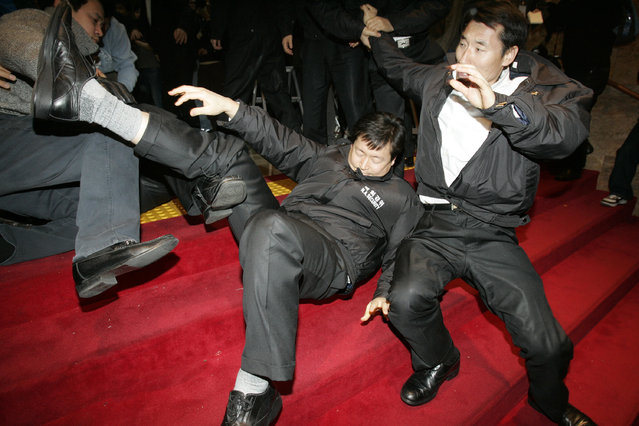 Parliament security guards fall during a scuffle with members of the main opposition Democratic Party at the National Assembly in Seoul, January 3, 2009. (Photo by Jo Yong-Hak/Reuters)