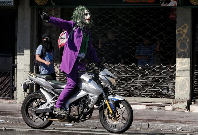 A protester dressed as a joker rides a motocycle during a protest against Chile's government in Valparaiso, Chile on October 28, 2019. (Photo by Rodrigo Garrido/Reuters)