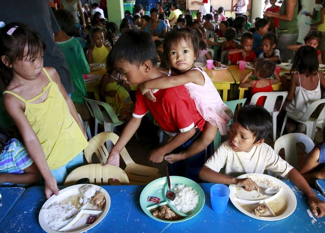 Children eat their free meals during a feeding program by outreach group World Mission Community Care at a slum area in Tondo city, metro Manila, July 20, 2015. Hunger in the Philippines decreased to its lowest level in 10 years as a recent survey showed a drop to 12.7 percent of families that were going hungry, or around 2.8 million households, in the second quarter of 2015, according to a poll by non-profit social research institution Social Weather Stations (SWS). (Photo by Romeo Ranoco/Reuters)
