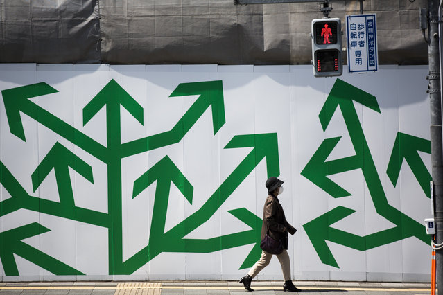 A pedestrian walks past decorated panelling used to shroud a construction site along a street in Tokyo on April 5, 2017. (Photo by Behrouz Mehri/AFP Photo)