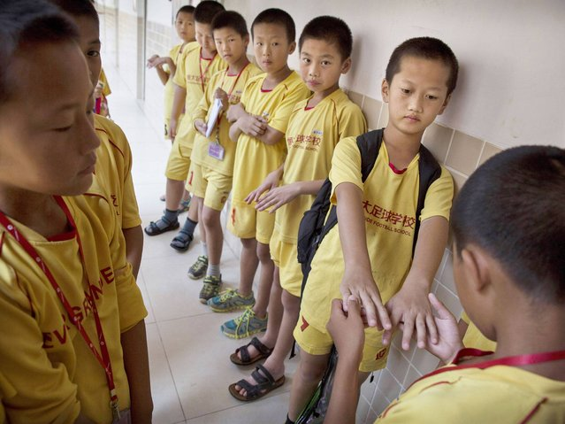 Young Chinese football players line-up to have their fingernails checked for cleanliness before training at the Evergrande International Football School near Qingyuan in Guangdong Province. (Photo by Kevin Frayer/Getty Images)
