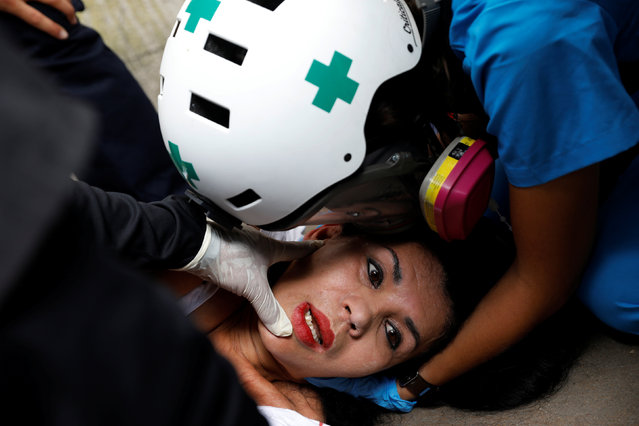 Volunteer members of a primary care response team help an injured demonstrator during the 'march of the empty pots' against Venezuelan President Nicolas Maduro's government in Caracas, Venezuela, June 3, 2017. (Photo by Carlos Garcia Rawlins/Reuters)