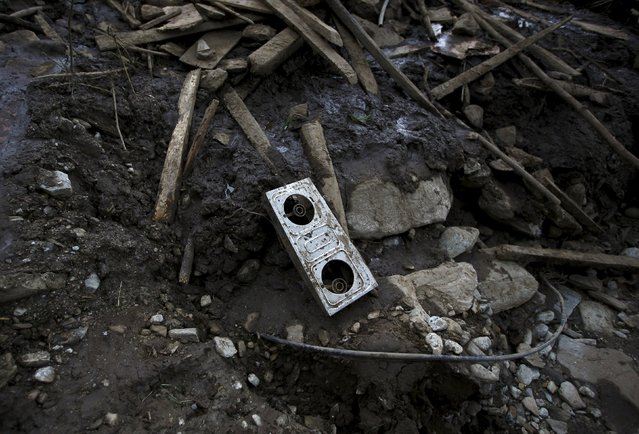 A gas stove lies on top of the pile of mud after the landslide at Lumle village in Kaski district July 30, 2015. (Photo by Navesh Chitrakar/Reuters)