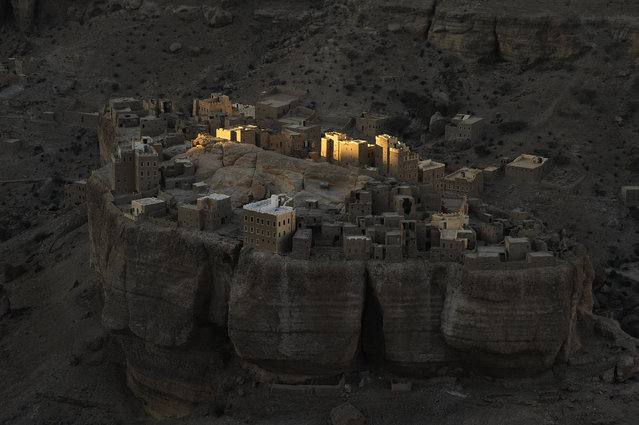 """Sunrise at Wadi Doan"". With my police escort I had arrived at my lodgings at dusk, perched on the edge of a massive escarpment in Yemen's Wadi Doan. In the fading light and on the valley floor I could see this fortresslike village. Having imagined how it might present under a rising sun, I was up at first light. Photo location: Haid Al-Jazil in Wadi Doan, Hadramaut, Yemen. (Photo and caption by Paul Nevin/National Geographic Photo Contest)"
