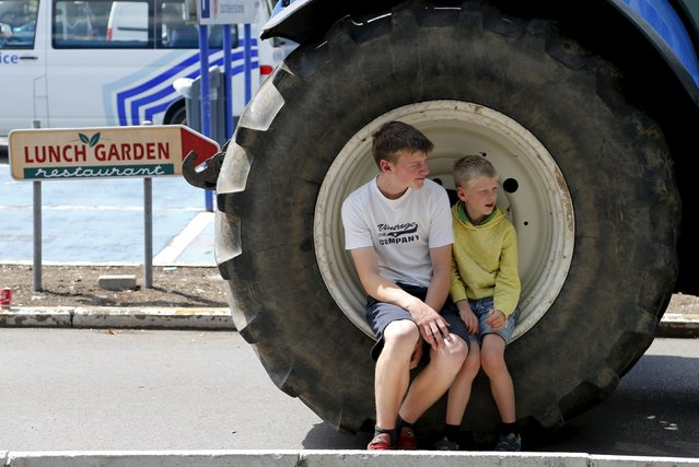 "Children sit on the wheel of a tractor as Belgian dairy farmers block the entrance of a Carrefour supermarket during a protest against low milk prices in Waterloo near Brussels, Belgium, July 31, 2015"". (Photo by Francois Lenoir/Reuters)"