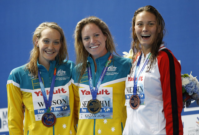 Australia's gold medal winner Emily Seebohm is flanked by Australia's silver medal winner Madison Wilson, left, and Denmark's bronze medal winner Mie Oe Nielsen during the ceremony for the women's 100m backstroke final at the Swimming World Championships in Kazan, Russia, Tuesday, August 4, 2015. (Photo by Sergei Grits/AP Photo)