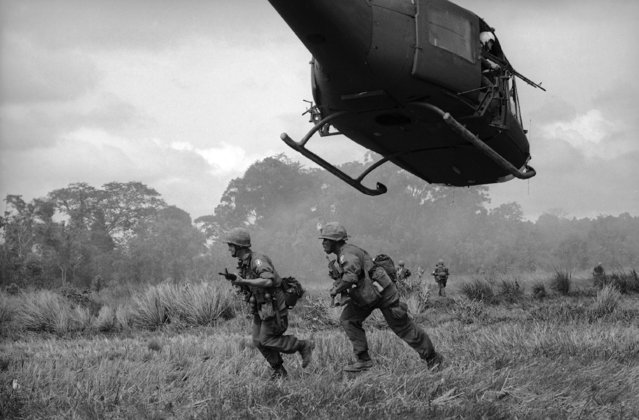 Paratroopers of the 173rd U.S. Airborne Brigade scurry through South Vietnam field after landing from helicopter near Saigon on May 31, 1965. The brigade launched its first major operational exercise but no major contact with the Viet Cong was reported. (Photo by Horst Faas/AP Photo)