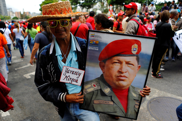 A pro-government supporter holds a picture of Venezuela's late President Hugo Chavez during a rally of members of the education sector in Caracas, Venezuela June 14, 2016. (Photo by Ivan Alvarado/Reuters)