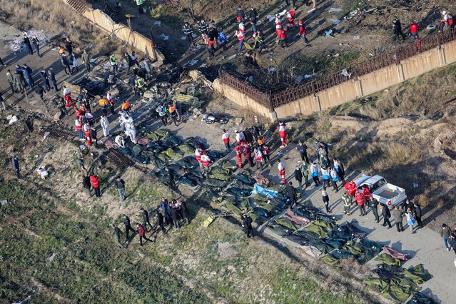 People and rescue teams are pictured amid bodies and debris after a Ukrainian plane carrying 176 passengers crashed near Imam Khomeini airport in the Iranian capital Tehran early in the morning on January 8, 2020, killing everyone on board. The Boeing 737 had left Tehran's international airport bound for Kiev, semi-official news agency ISNA said, adding that 10 ambulances were sent to the crash site. (Photo by Rouhollah Vahdati/ISNA via AFP Photo)