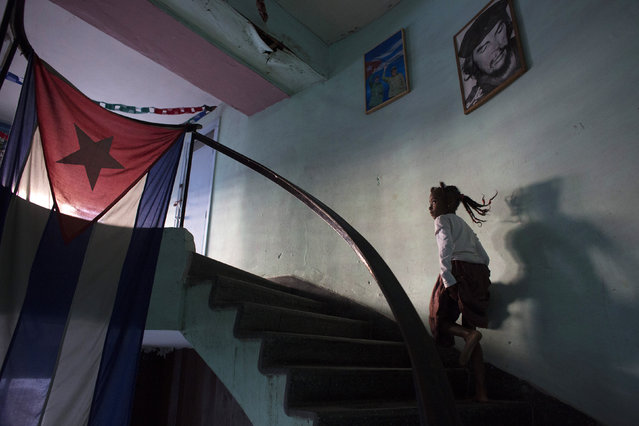 """Sakia Corona, 8, passes a picture of Cuba's revolutionary hero Ernesto """"Che"""" Guevara as she runs to a restroom during a rehearsal of a Contemporary Haitian dance in a communal center in downtown Havana, January 31, 2015. (Photo by Alexandre Meneghini/Reuters)"""