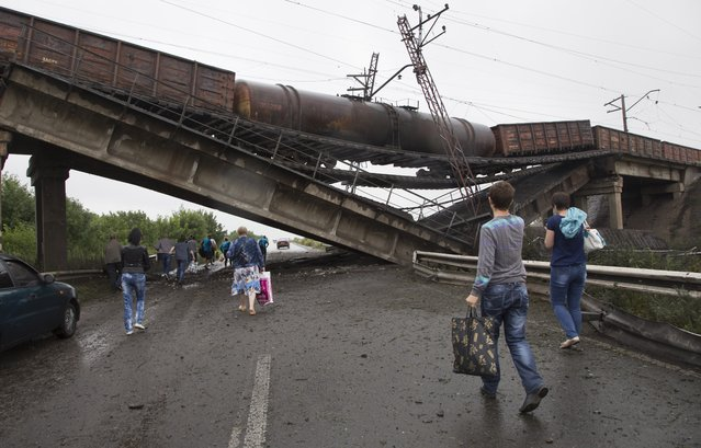 People walk under a destroyed railroad bridge over a main road leading into the east Ukraine city of Donetsk, near the village of Novobakhmutivka, 20 km North from the city of Donetsk, eastern Ukraine Monday, July 7, 2014. The bridge has been destroyed, blocking a key access route to the rebel-held city. (Photo by Dmitry Lovetsky/AP Photo)