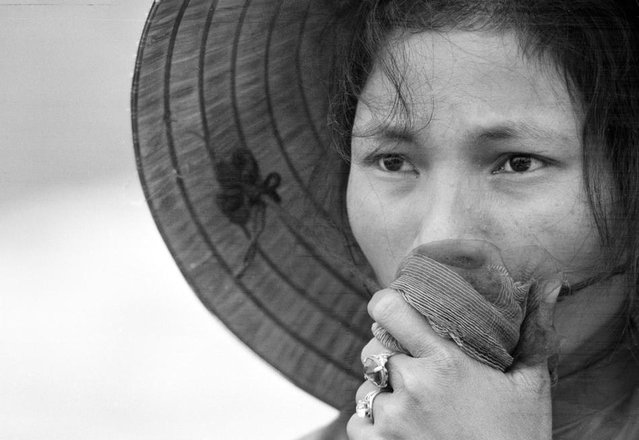A young South Vietnamese woman covers her mouth as she stares into a mass grave where victims of a reported Viet Cong massacre were being exhumed near Dien Bai village, east of Hue, in April 1969