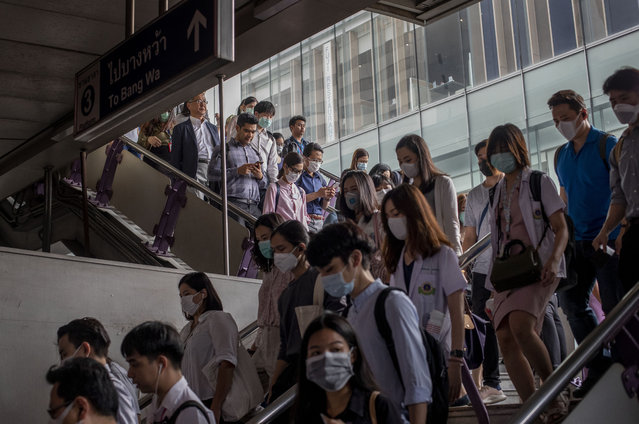 Commuters wear face masks to protect themselves from air pollution and the spreading coronavirus in Bangkok, Thailand, Tuesday, February 4, 2020. On Tuesday, the Korea Centers for Disease Control and Prevention said a 42-year-old South Korean woman tested positive for the virus, days after she returned from a trip to Thailand with chills and other symptoms. (Photo by Gemunu Amarasinghe/AP Photo)