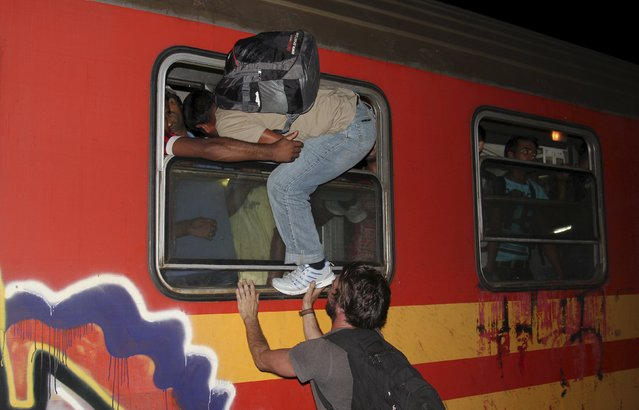 Migrants try to board a train at Gevgelija train station in Macedonia, close to the border with Greece, August 14, 2015. (Photo by Fatos Bytyci/Reuters)