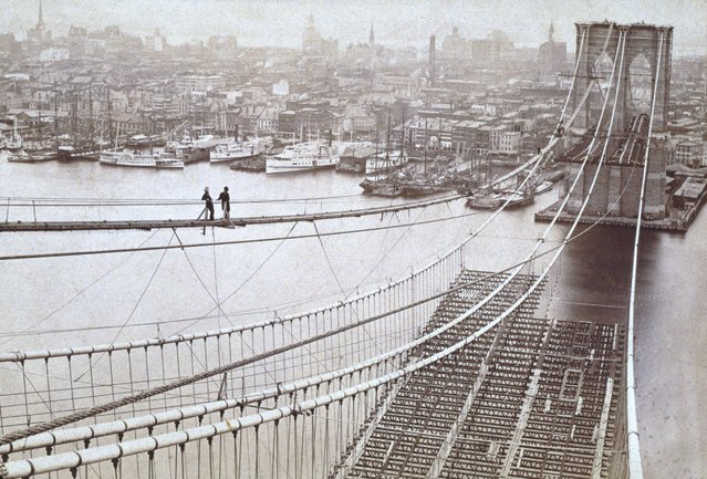 Two men standing on a high catwalk, surveying the construction of the Brooklyn Bridge, with Manhattan in the background, New York City, 1877. (Photo by Museum of the City of New York/Archive Photos/Getty Images)