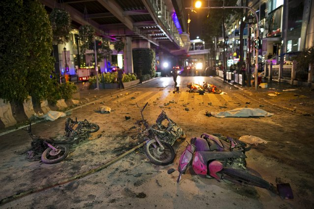 Wreckage of motorcycles are seen as security forces and emergency workers gather at the scene of a blast in central Bangkok August 17, 2015. (Photo by Athit Perawongmetha/Reuters)