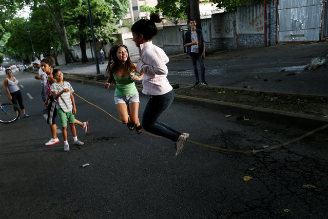Girls skip on a street blocked by barricades during clashes at a rally against President Nicolás Maduro's government in Caracas, Venezuela on July 19, 2017. (Photo by  Andres Martinez Casares/Reuters)
