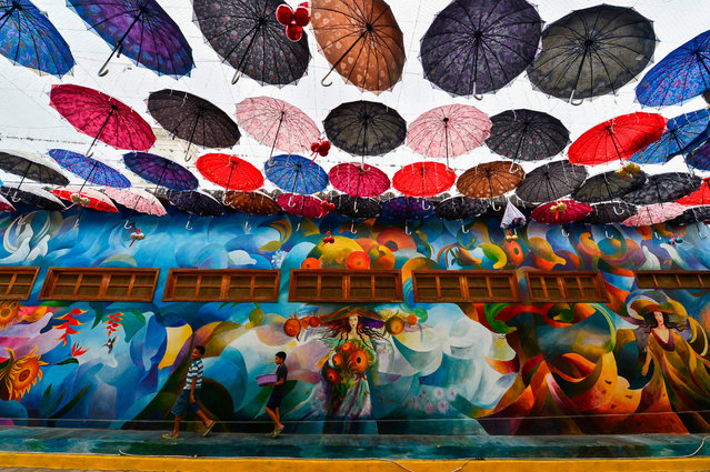 Two kids walk by a centric avenue covered with umbrellas in Cantarranas, Honduras, on January 7, 2020. Cantarranas, a small municipality near Tegucigalpa, has converted into a permanent exhibition of open-air art. (Photo by Orlando Sierra/AFP Photo)