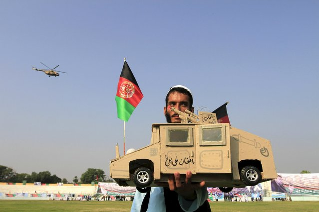 An Afghan man holds a small handmade armoured vehicle during a ceremony marking Afghanistan's 96th Independence Day in Jalalabad province, Afghanistan August 19, 2015. (Photo by Reuters/Parwiz)