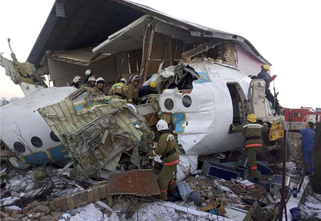In this handout photo provided by the Emergency Situations Ministry of the Republic of Kazakhstan, police and rescuers work on the side of a plane crash near Almaty International Airport, outside Almaty, Kazakhstan, Friday, December 27, 2019. Almaty International Airport said a Bek Air plane crashed Friday in Kazakhstan shortly after takeoff causing numerous deaths. The aircraft had 100 passengers and crew onboard when hit a concrete fence and a two-story building shortly after takeoff. (Photo by Emergency Situations Ministry of the Republic of Kazakhstan Photo via AP Photo)