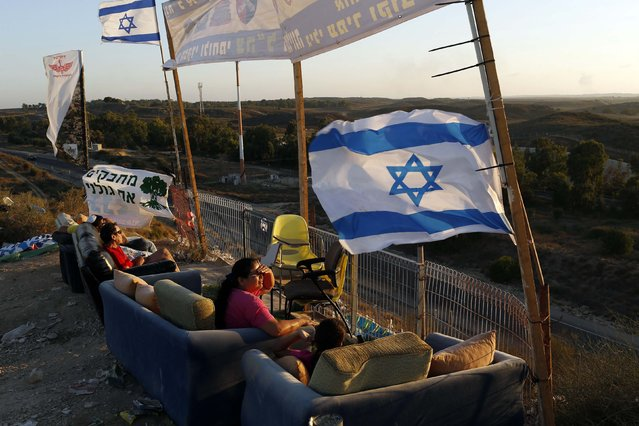 Israelis watch the latest military activity towards Gaza, August 2, 2014. Some Israeli ground forces withdrew from the Gaza Strip on Saturday, two Israeli television stations reported, after the military said it was close to achieving its main war goal of destroying Hamas cross-border tunnels. (Photo by Siegfried Modola/Reuters)