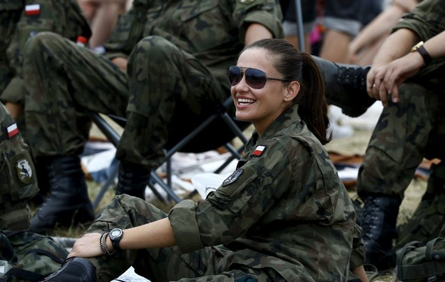 A soldier from a military base in Wegorzewo smiles as she attends an airplane performance at the Radom Air Show at an airport in Radom, Poland August 23, 2015. (Photo by Kacper Pempel/Reuters)