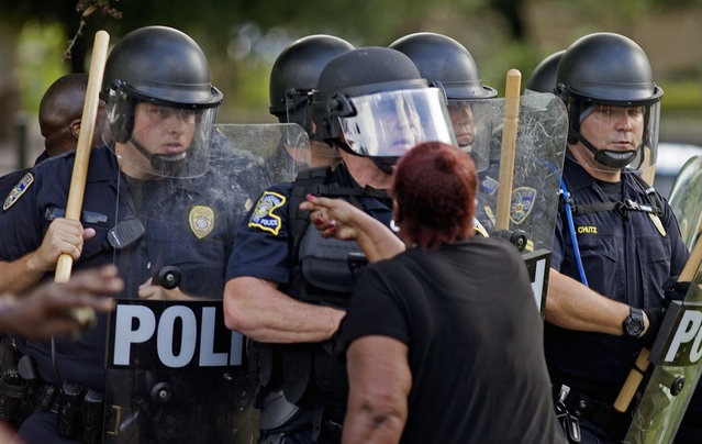 A protester yells at police in front of the Baton Rouge Police Department headquarters after police arrived in riot gear to clear protesters from the street in Baton Rouge, La., July 9, 2016. Several protesters were arrested. (Photo by Max Becherer/AP Photo)