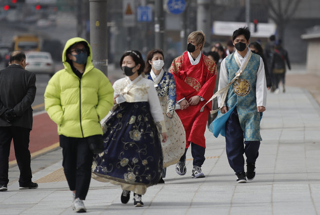Visitors wearing face masks walk near the Gwanghwamun, the main gate of the 14th-century Gyeongbok Palace, and one of South Korea's well-known landmarks, in Seoul, South Korea, Saturday, February 22, 2020. South Korea on Saturday reported a six-fold jump in viral infections in four days to 346, most of them linked to a church and a hospital in and around the fourth-largest city where schools were closed and worshipers and others told to avoid mass gatherings. (Photo by Lee Jin-man/AP Photo)