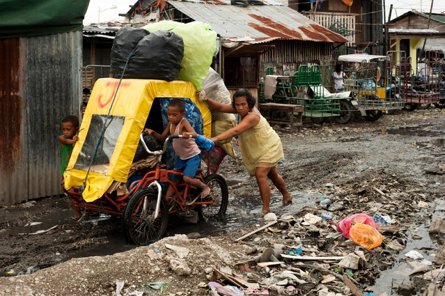 A scavenger and her children push a pedicab through mud at a settler community on August 11, 2014 in Manila, Philippines. (Photo by Dondi Tawatao/Getty Images)