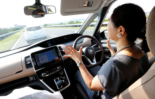 Reuters auto correspondent Maki Shiraki removes her hands from the steering wheel as she test drives Nissan's new Serena minivan, which is equipped with Propilot semi-automated driving functions, at the company's test drive facility in Yokosuka, Japan July 12, 2016. Nissan Motor Co Ltd launched a suite of semi-autonomous driving functions on Wednesday stressing they were intended to assist and not replace drivers, just two weeks after similar technology in another maker's car was involved in a fatal crash. (Photo by Toru Hanai/Reuters)