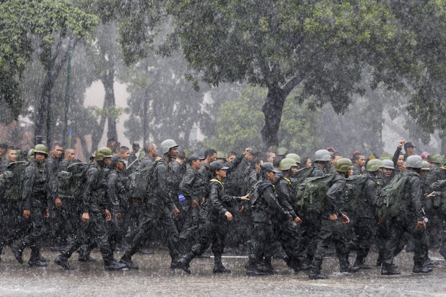 In this August 26, 2017 photo, soldiers march during a military drill in Caracas, Venezuela. Supporters of Venezuela's President Nicolas Maduro and civilian militias marched alongside soldiers to denounce U.S. economic sanctions and express support for military exercises in defiance of President Donald Trump warning of possible military action to resolve the country's crisis. (Photo by Ricardo Mazalan/AP Photo)