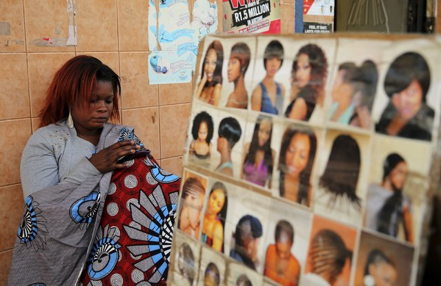 A hairdresser uses her phone as she waits for clients at a makeshift saloon in Soweto, August 4, 2014. Market research firm Euromonitor International sees the liquid haircare market growing by about 5 percent from 2013 to 2018 in Nigeria and Cameroon, with a slight decline for the more mature South African market. (Photo by Siphiwe Sibeko/Reuters)