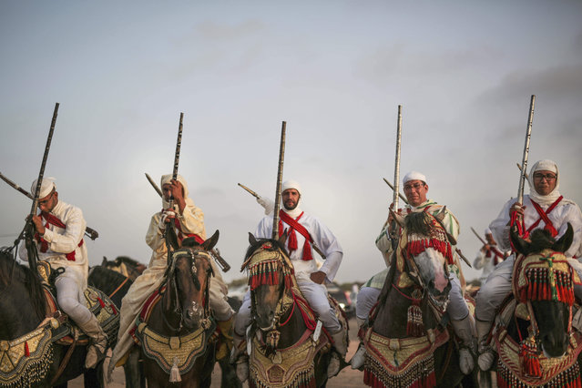 In this Thursday, August 17, 2017 photo, horsemen prepare to take part in Tabourida, a traditional horse riding show also known as Fantasia, in Mansouria, near Casablanca, Morocco. (Photo by Mosa'ab Elshamy/AP Photo)