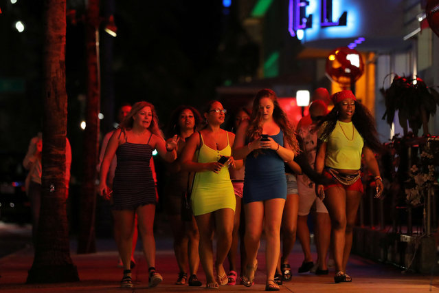 University students walk along a street of Miami Beach during Spring Break after local authorities closed restaurants, bars, gyms, movie theaters and other similar businesses and rolled out a midnight curfew along South Beach's busiest strips for precaution due to coronavirus disease (COVID-19) spread, in Miami Beach, Florida, U.S., March 18, 2020. (Photo by Carlos Barria/Reuters)