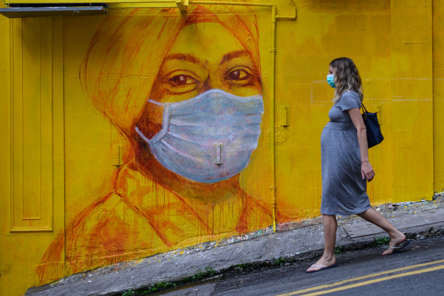 A pregnant woman wearing a face mask as a precautionary measure walks past a street mural in Hong Kong, on March 23, 2020, after the city's Chief Executive announced plans to temporarily ban the sale of alcohol in bars and restaurants as a measure to help stop the spread of the COVID-19 caused by the novel coronavirus. Hong Kong will ban all non-residents from entering the city from midnight on March 24, 2020 in a bid to halt the coronavirus, its leader says, as she unveils plans to stop restaurants and bars serving alcohol. (Photo by Anthony Wallace/AFP Photo)