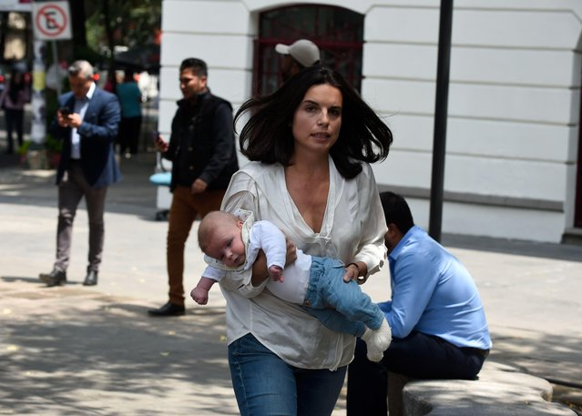 A woman rushes with her baby along the streets after a quake rattled Mexico City on September 19, 2017. (Photo by Alfredo Estrella/AFP Photo)