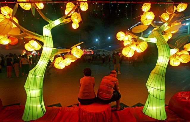 This photo taken on Saturday Jan. 24, 2009 in Singapore shows an elderly couple sitting under lantern sculptures of mandarin orange trees as they gather to usher in the eve of the Chinese Lunar New Year. (Photo by Wong Maye-E/AP Photo)