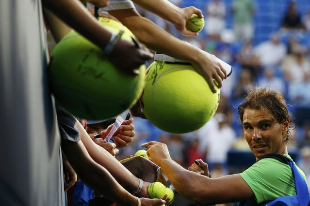 Rafael Nadal of Spain signs autographs for fans following his victory over Diego Schwartzman of Argentina during their second round match at the U.S. Open Championships tennis tournament in New York, September 2, 2015. (Photo by Shannon Stapleton/Reuters)