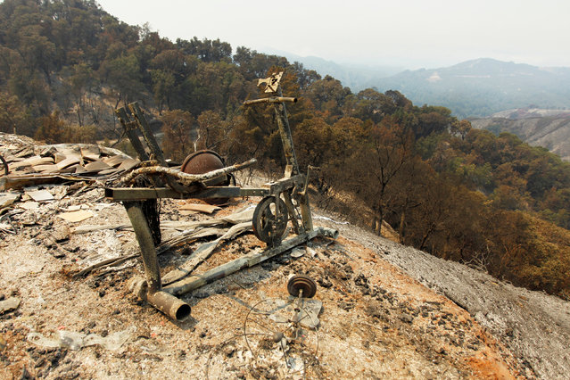 An exercise bike sits on the edge of a slope at the site of a destroyed house after the Soberanes Fire burned through the Palo Colorado area, north of Big Sur, California, July 31, 2016. (Photo by Michael Fiala/Reuters)