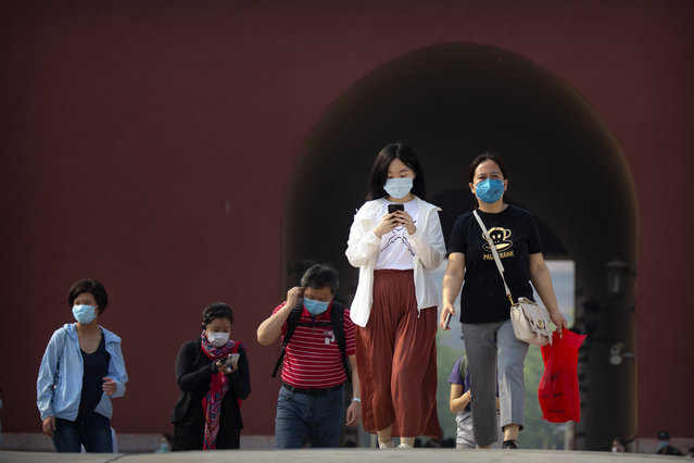 Visitors wearing face masks to protect against the new coronavirus walk through the Forbidden City in Beijing, Friday, May 1, 2020. (Photo by Mark Schiefelbein/AP Photo)
