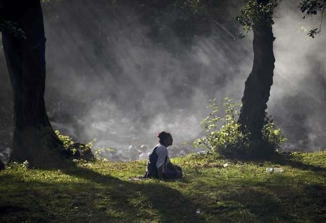 The sun rays are filtered through smoke as a Romanian Roma sits on the grass while the Roma community celebrates the Birth of the Virgin Mary in Costesti, Romania, Monday, September 8, 2014. (Photo by Vadim Ghirda/AP Photo)