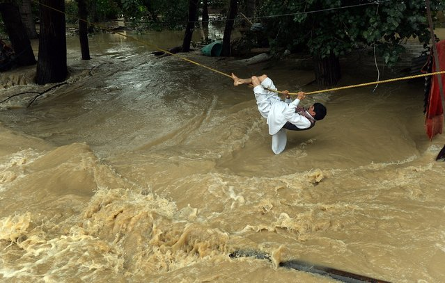 An Indian Kashmiri man crosses over flood waters with the use of a rope in Srinagar on September 9, 2014.  Bewildered families, nursing children and clutching meagre belongings, packed into makeshift relief centres after fleeing floods in India and Pakistan that have now claimed more than 400 lives. (Photo by Punit Paranjpe/AFP Photo)
